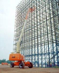 JLG Aerial work platform extended next to tall building under construction