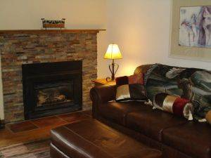 Mountain Side Condo #211C Family Room with fireplace and leather couch