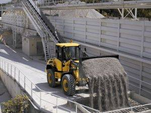 Compact Wheel Loader dumping concrete for job
