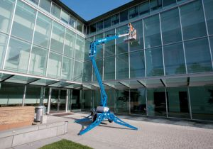 Genie TZ3420 Towable Boom Lift used to clean windows of commercial building