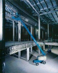 Genie straight boom lift being used in warehouse for high reach electrical work