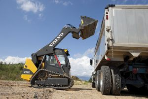 Compact Track Loader loading dirt in dump truck