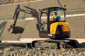 Volvo Mini Excavator digging next to fence