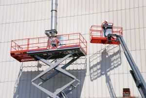 Skyjack Scissor lift and boom lift elevating men working on side of building