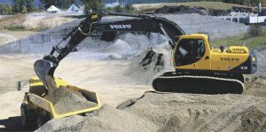 Excavator Giving a Dump Truck a Full Load of Gravel