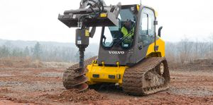 Compact Track Loader with Auger Attachment drilling hole on jobsite