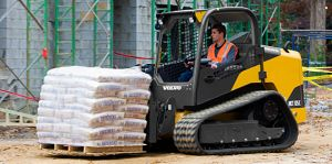Compact Track Loader with Pallet Fork Attachment delivering construction supplies