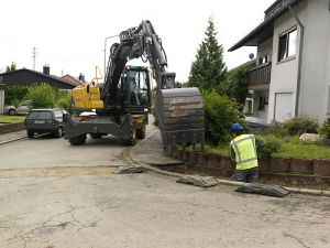 Wheeled Excavator working on road by house in tight space